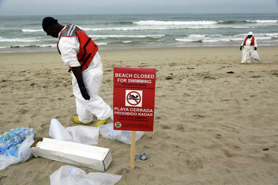 A cleanup crew collects balls of tar that washed ashore in Manhattan Beach, Calif., on Thursday. Photo: Nick Ut — The Associated Press   / AP