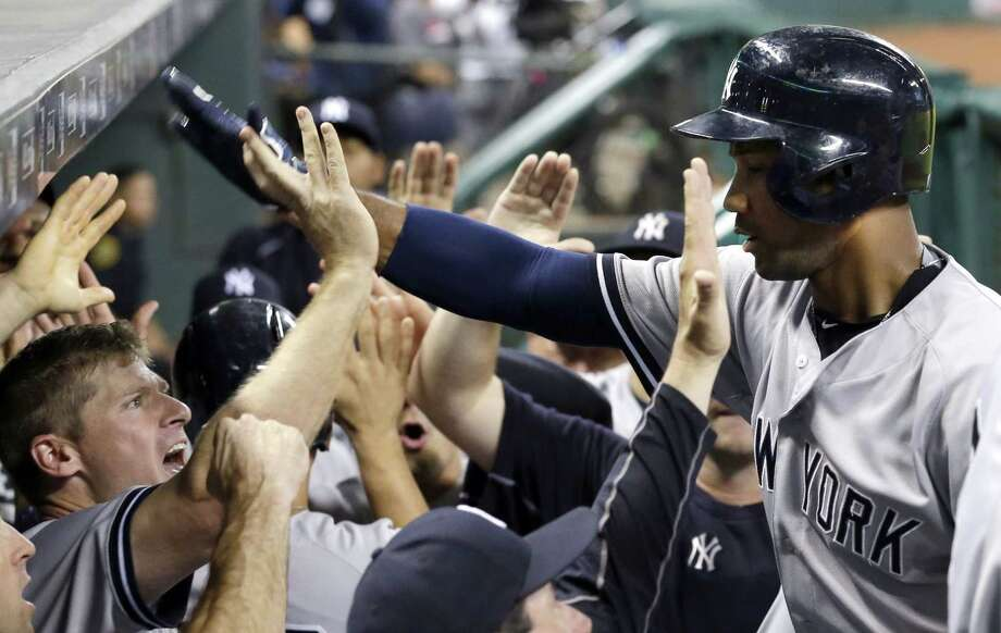 The Yankees' Chris Young, right, is congratulated as he returns to the dugout after hitting a three-run home run against the Houston Astros. Photo: David J. Phillip  — The Associated Press   / AP