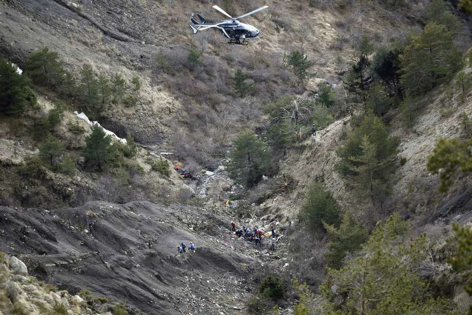 FILE - In this Thursday March 26, 2015 file photo, a helicopter flies over rescue workers at the crash site of the Germanwings jet near Seyne-les-Alpes, France. The somber mission to recover the remains of 150 people killed instantly when the Germanwings flight slammed full speed into the Col de Mariaud is not a quiet one and crucial physical evidence for the crash investigation can be gathered only when the mountains cooperate. (AP Photo/Laurent Cipriani, File) Photo: AP / AP