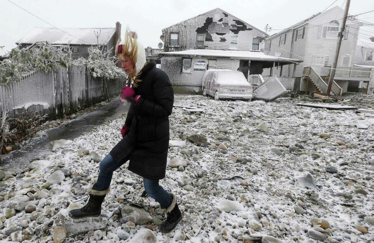 FILE - In this Tuesday, Jan. 27, 2015 file photo, Lynn Leary walks past houses damaged by ocean waves during a winter storm in Marshfield, Mass. New Englandís epic winter is on pace to produce an epic number of insurance claims. Thousands of homeowners are filing claims as they begin to repair the damage brought by an especially brutal winter. (AP Photo/Michael Dwyer, File)