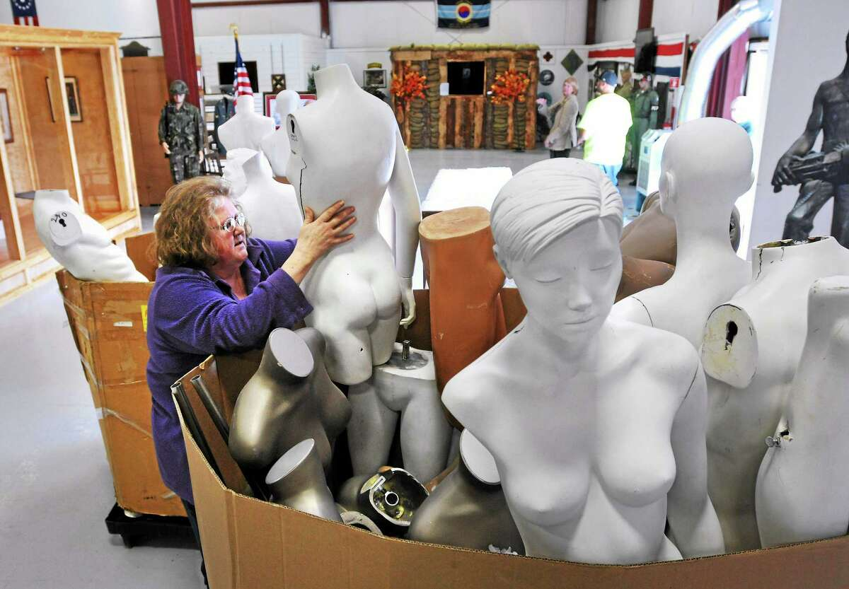 (Peter Casolino-New Haven Register) Lori Grenfell, a board member and volunteer at the West Haven Veterans Museum & Learning Center, looks over some mannequins donated to the museum by Macy's in New York. The mannequins are dressed in military uniforms from all periods in history to show visitors historic clothing. 4/9/14