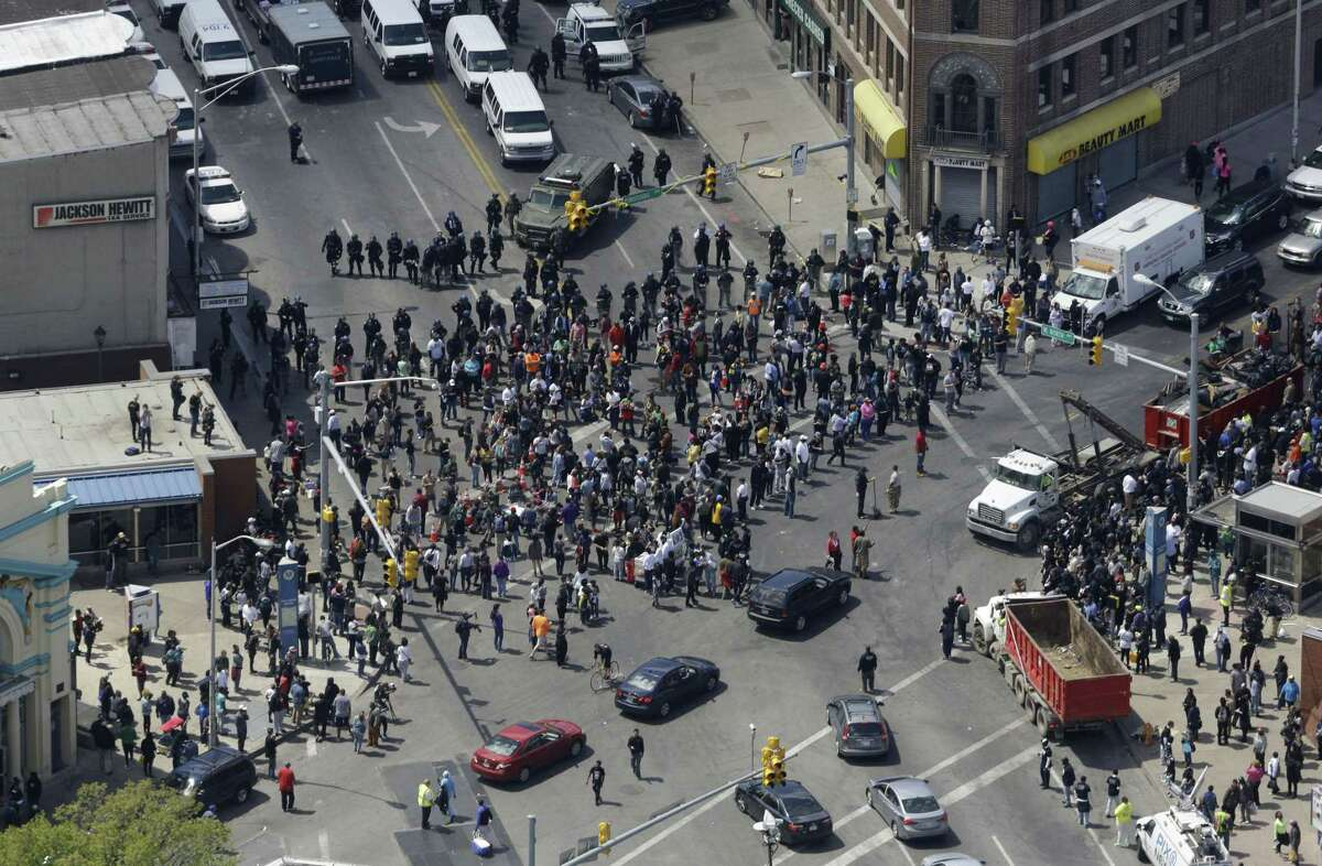 Police stand in formation near a gathering of protestors at the intersection of North Avenue and Pennsylvania Avenue, Tuesday, April 28, 2015, in Baltimore, a day following unrest that occurred after Freddie Gray's funeral. Gray died from spinal injuries about a week after he was arrested and transported in a Baltimore Police Department van.