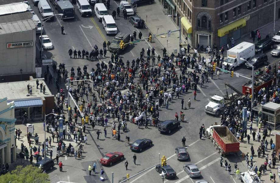 Police stand in formation near a gathering of protestors at the intersection of North Avenue and Pennsylvania Avenue, Tuesday, April 28, 2015, in Baltimore, a day following unrest that occurred after Freddie Gray's funeral. Gray died from spinal injuries about a week after he was arrested and transported in a Baltimore Police Department van. Photo: (AP Photo/Patrick Semansky) / AP