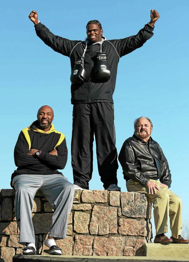 Former University of New Haven basketball star Cassius Chaney, now a professional boxer, poses with his managers Vin Baker of Old Saybrook, a former NBA standout, left, and Allen Hadelman, right. Photo: Peter Hvizdak — Register   / ©2015 Peter Hvizdak