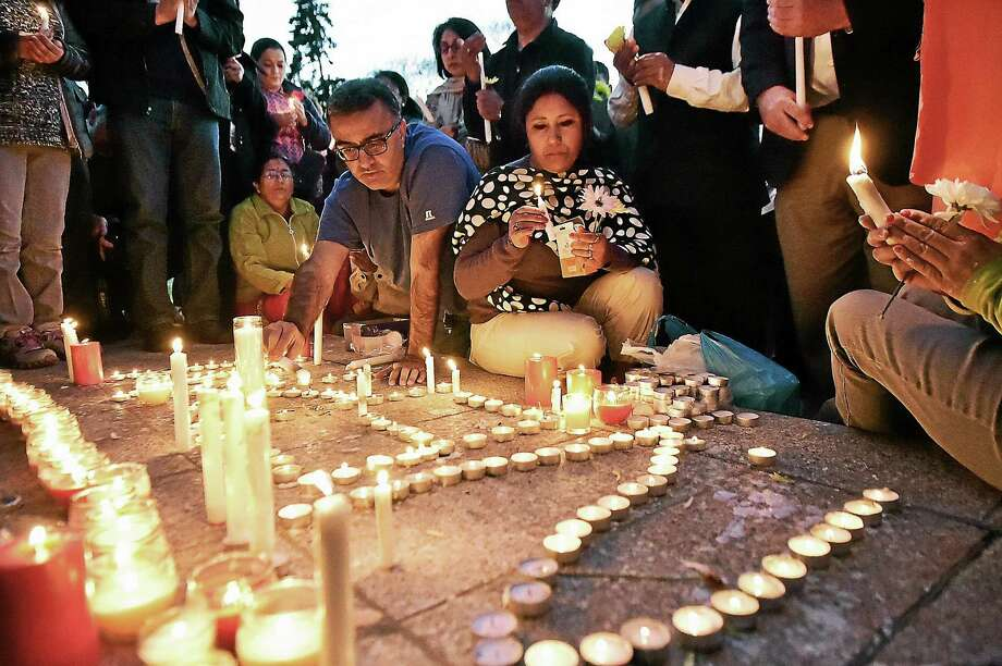 """Branford residents Mamata K. Thakur, formerly of Nepal, front, and Mahesh Kumar, formerly of Pakistan, light candles which spell out """"Nepal"""" during a candlelight vigil Tuesday in Branford. Photo: Catherine Avalone — New Haven Register   / New Haven RegisterThe Middletown Press"""