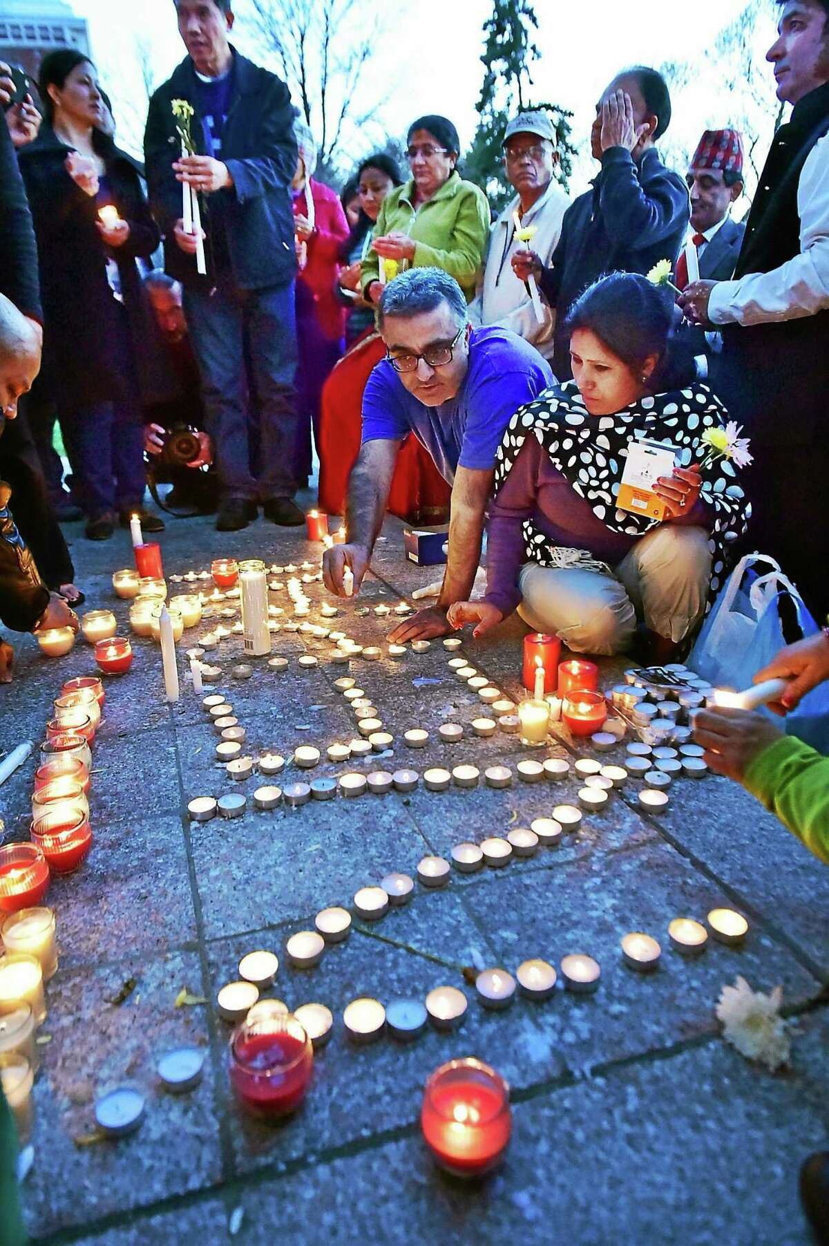 """Branford residents Mamata K. Thakur, formerly of Nepal, front, and Mahesh Kumar, formerly of Pakistan, light candles which spell out """"Nepal"""" during a candlelight vigil Tuesday in Branford."""