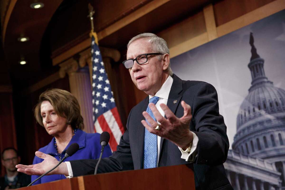 In this Feb. 26 file photo, Senate Minority Leader Harry Reid of Nevada, accompanied by House Minority Leader Nancy Pelosi of California, gestures during a news conference on Capitol Hill in Washington.