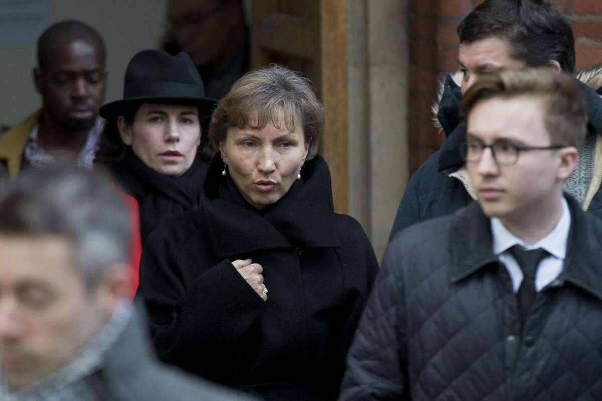"""Marina Litvinenko, center, the widow of former Russian intelligence officer Alexander Litvinenko, and their son Anatoly, right, leave for the lunch break in proceedings at the Royal Courts of Justice in London on Jan. 27, 2015. A British judge opened an inquiry Tuesday into the death of Alexander Litvinenko, declaring the issues raised in the poisoning death of the former Russian intelligence agent to be of the """"utmost gravity."""""""