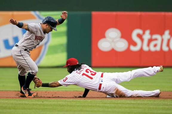 Houston Astros' Jose Altuve, left, tries to get away from a tag by Philadelphia Phillies shortstop Freddy Galvis, right, after he overran second base during the first inning of a baseball game, Monday, July 24, 2017, in Philadelphia. Altuve was out on the play. (AP Photo/Chris Szagola)