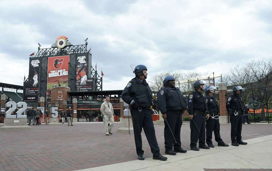 Baltimore police officers stand guard outside of Oriole Park at Camden Yards on Monday in Baltimore. Photo: Nick Wass — The Associated Press   / FR67404 AP