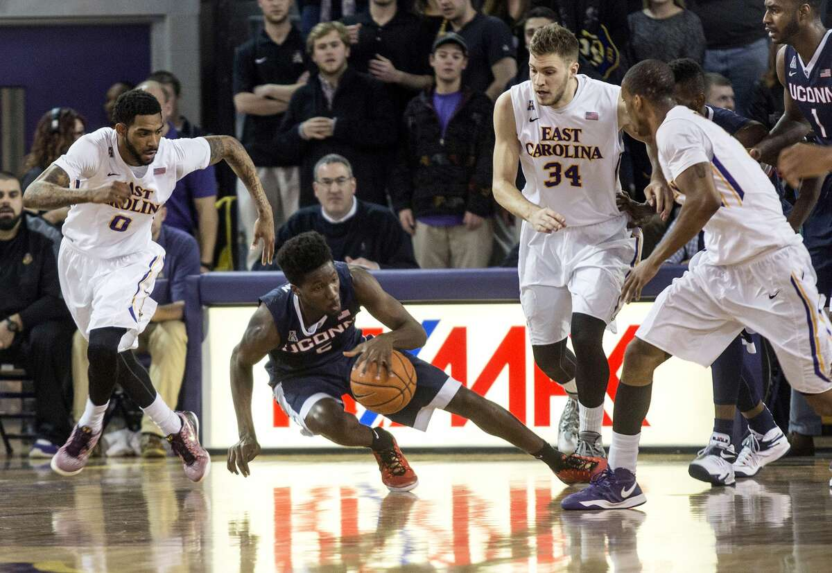 UConn guard Daniel Hamilton (5) goes after the ball as Eastern Carolina's Terry Whisnant (0) and Michael Zangari (34) defend during the first half of Wednesday's game at Minges Coliseum in Greenville, N.C.