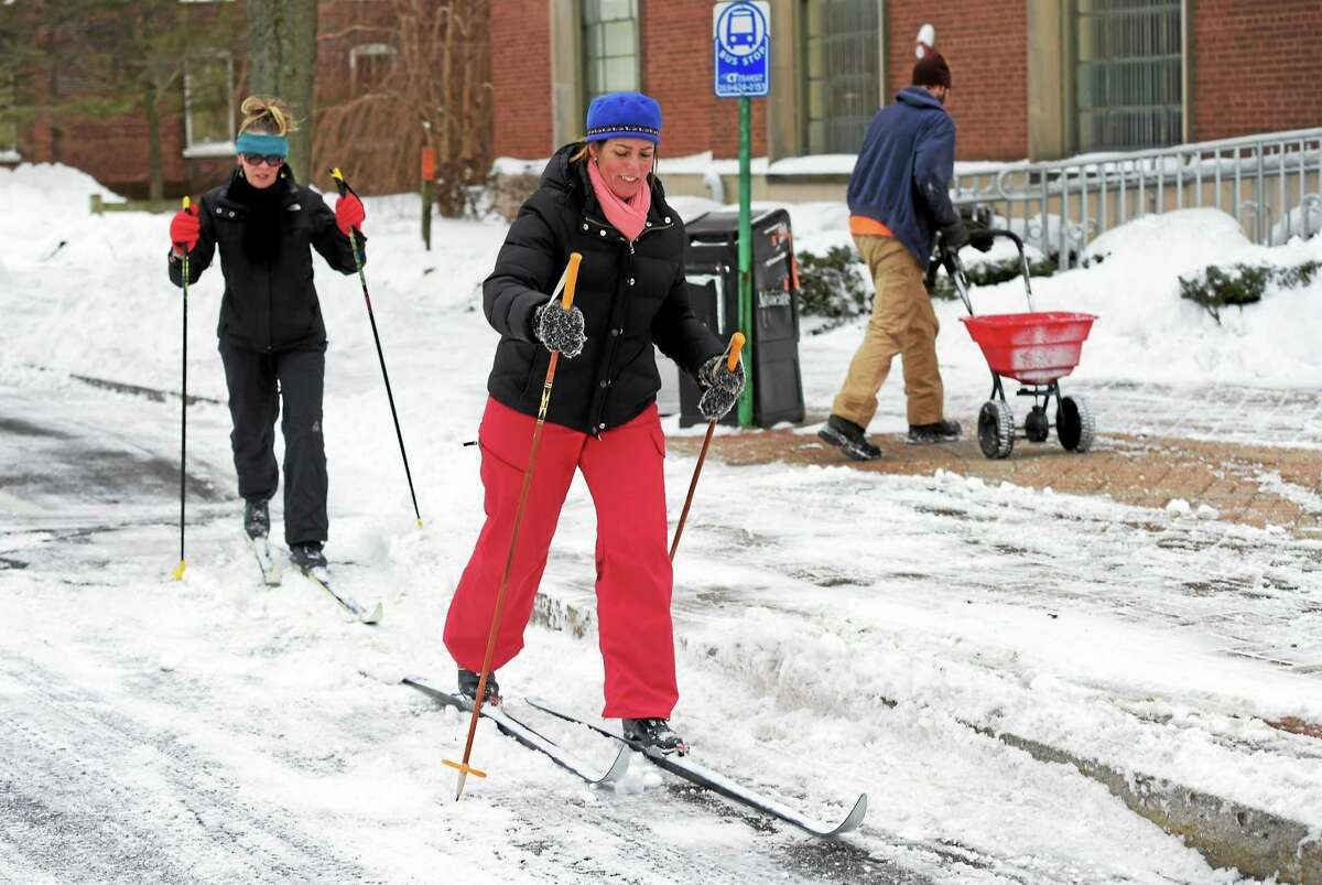(Peter Hvizdak - New Haven Register) Susan Borger, left, and friend Marsha Hall, both of Branford, uses cross country skis to travel on Main Street in Branford, Conn. in the aftermath of the Blizzard Tuesday, January 27, 2015.