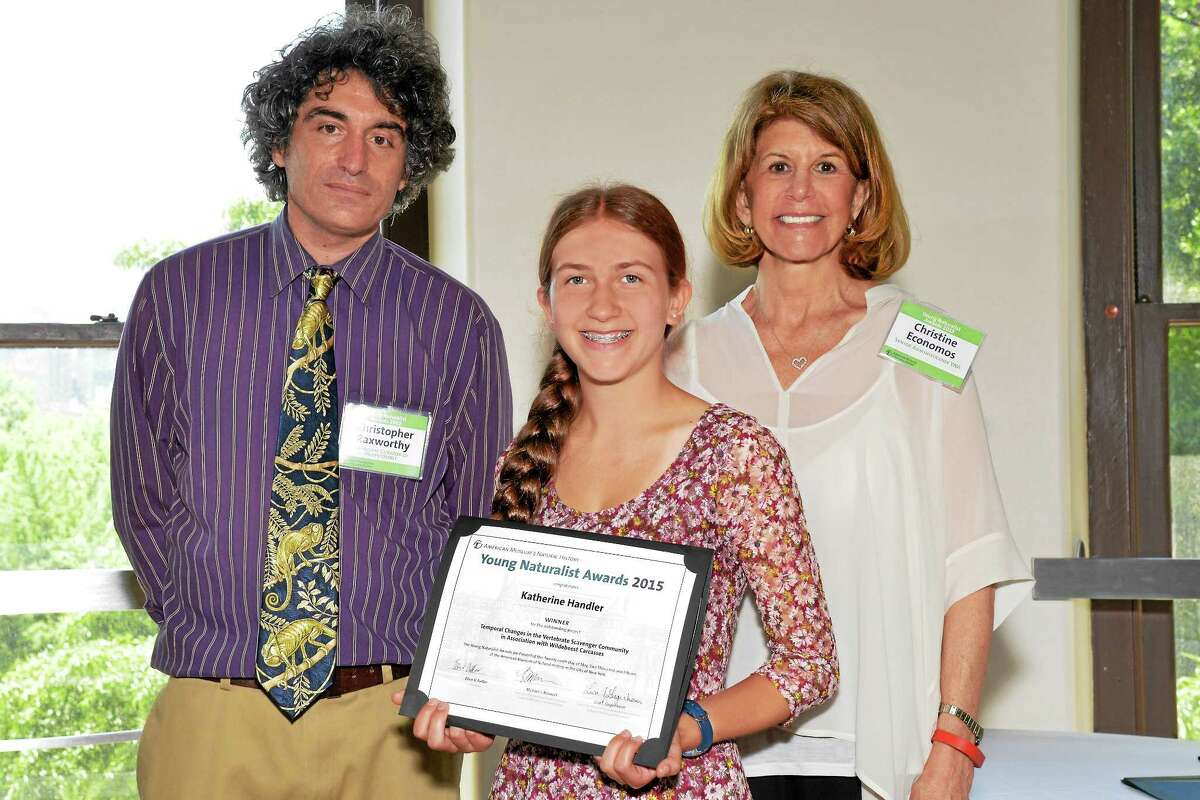 PHOTO COURTESY AMNH/D. FINNIN Amity student Katherine Handler, middle, receives her 2015 Young Naturalists Award during a recent ceremony at the American Museum of Natural History in New York City. Presenting the award certificate were, from left, Christopher Raxworthy, associate curator in the Department of Herpetology and associate dean of Science for Education and Exhibitions; and Christine Economos, senior program administrator for the Young Naturalists Awards.