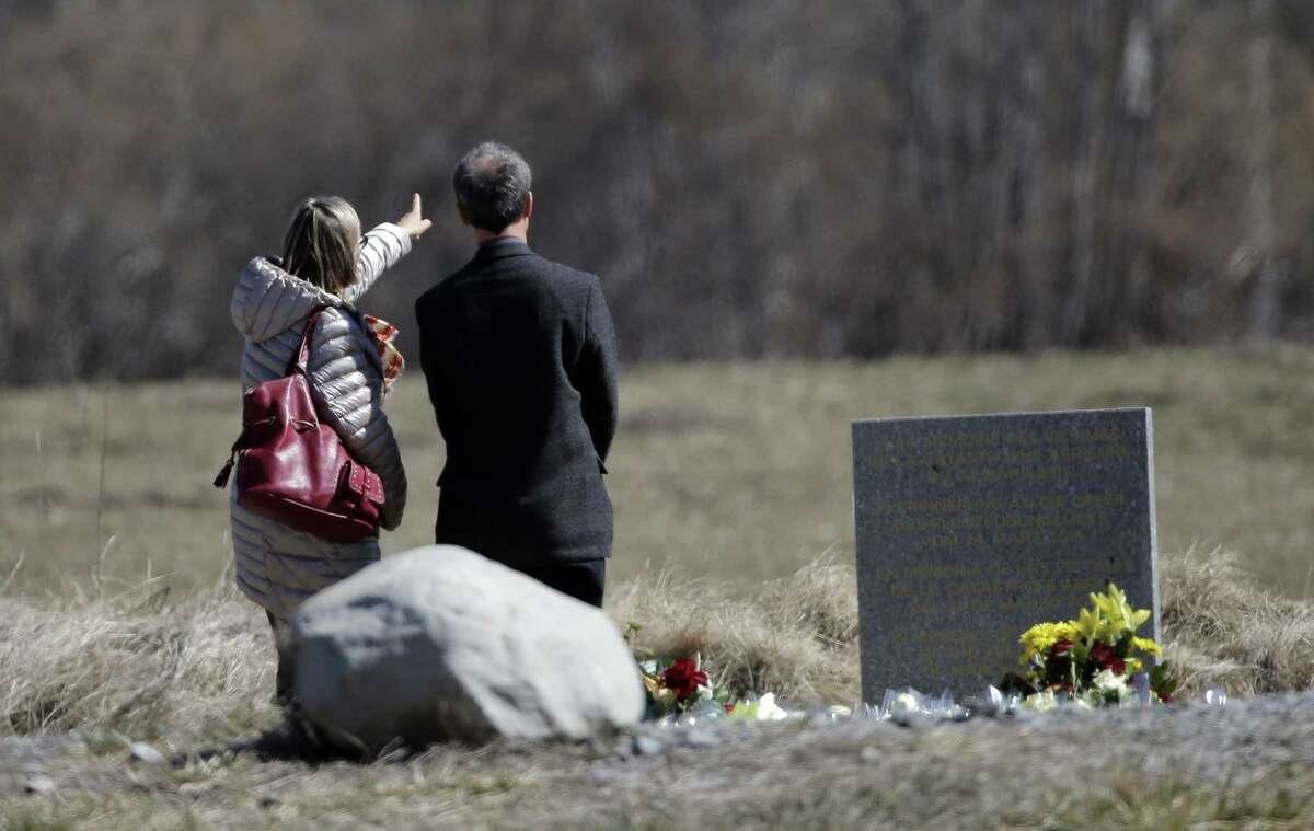 People pay tribute next to a stele and flowers laid in memory of the victims in the area where the Germanwings jetliner crashed in the French Alps, in Le Vernet, France, Friday, March 27, 2015. The crash of Germanwings Flight 9525 into an Alpine mountain, which killed all 150 people aboard, has raised questions about the mental state of the co-pilot. Authorities believe the 27-year-old German deliberately sought to destroy the Airbus A320 as it flew Tuesday from Barcelona to Duesseldorf. (AP Photo/Christophe Ena)