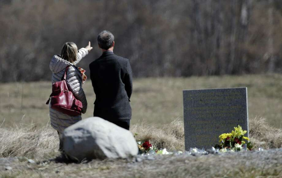 People pay tribute next to a stele and flowers laid in memory of the victims in the area where the Germanwings jetliner crashed in the French Alps, in Le Vernet, France, Friday, March 27, 2015. The crash of Germanwings Flight 9525 into an Alpine mountain, which killed all 150 people aboard, has raised questions about the mental state of the co-pilot. Authorities believe the 27-year-old German deliberately sought to destroy the Airbus A320 as it flew Tuesday from Barcelona to Duesseldorf. (AP Photo/Christophe Ena) Photo: AP / AP