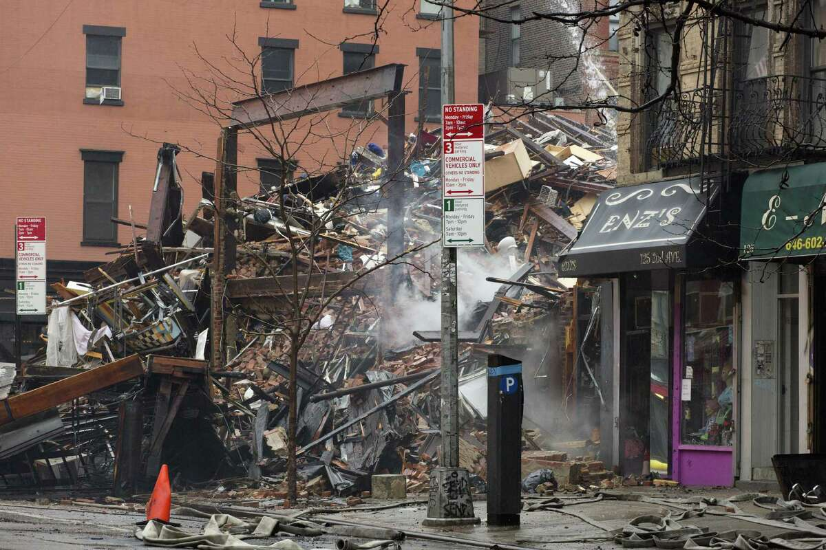 Debris from collapsed buildings smolders in the East Village neighborhood of New York, Friday, March 27, 2015. Authorities say two people are unaccounted for following an apparent gas explosion that leveled three buildings. Preliminary evidence suggested a gas explosion amid plumbing and gas work inside the building was to blame. (AP Photo/Mark Lennihan)