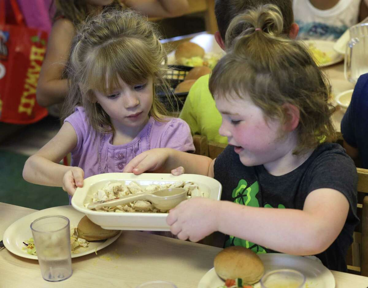 Rebekah Webb, left, shares a family-style meal with Zoe Turner during lunch with other 5-year-olds at the Olathe Family YMCA in Olathe, Kan., Wednesday, June 24, 2015. As early childhood teachers lament toddlers too large to fit in playground swings, officials are mulling changes designed to make meals served to millions of kids in day care healthier.