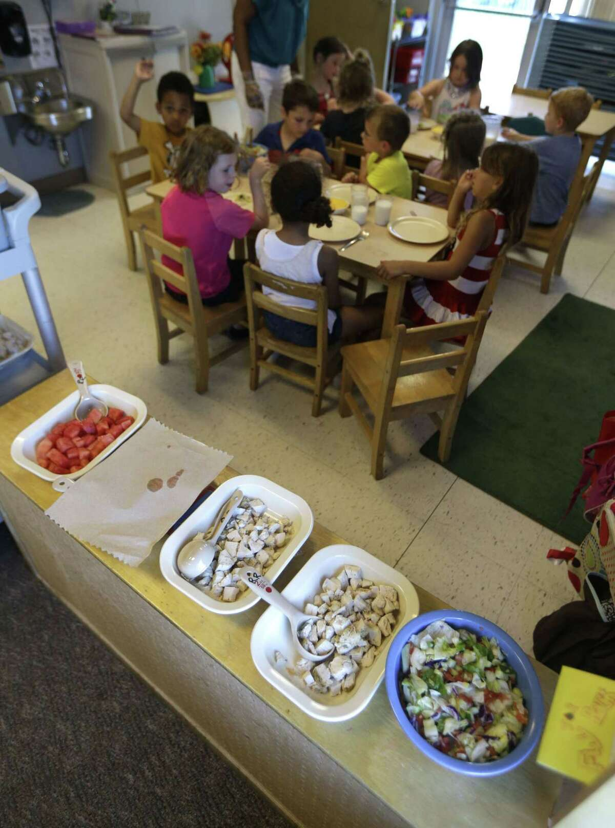 A family-style meals is served to a class of 4 and 5 year olds at the Olathe Family YMCA in Olathe, Kan., Wednesday, June 24, 2015. As early childhood teachers lament toddlers too large to fit in playground swings, officials are mulling changes designed to make meals served to millions of kids in day care healthier.