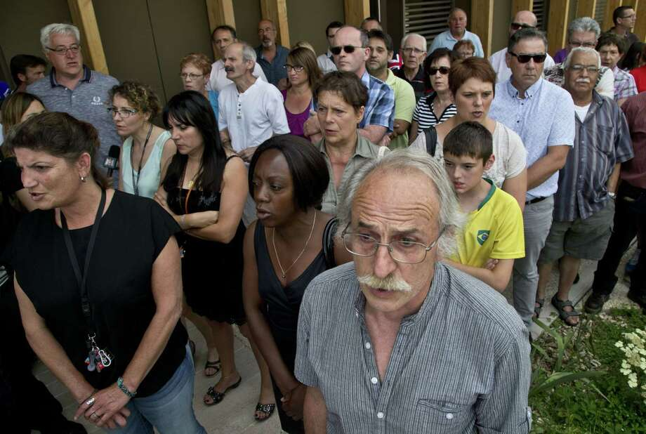People observe a minutes of silence in Quentin-Fallavier, southeast of Lyon, France, Saturday June 27, 2015, to pay their respects to the victim of the attack which took place yesterday in Saint-Quentin-Fallavier, June 26. A spokeswoman for the Paris prosecutor's office says one of the four suspects detained over an explosion and beheading in southeast France has been released, while the suspected assassin isn't speaking to investigators. Photo: (AP Photo/Michel Euler) / AP