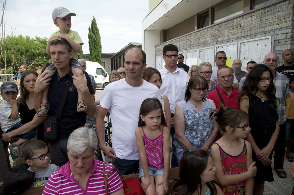 People observe a silence in Quentin-Fallavier, southeast of Lyon, France, Saturday June 27, 2015, to pay their respects to the victim of the attack which took place yesterday in Saint-Quentin-Fallavier, June 26. A spokeswoman for the Paris prosecutor's office says one of the four suspects detained over an explosion and beheading in southeast France has been released, while the suspected assassin isn't speaking to investigators.
