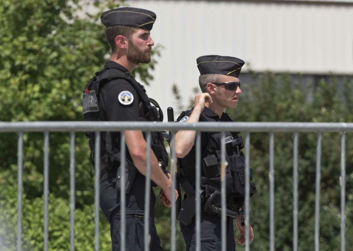 Police officers guard a road leading to a plant which was attacked on Friday in Saint-Quentin-Fallavier, southeast of Lyon, France, Saturday, June 27, 2015. A spokeswoman for the Paris prosecutor's office says one of the four suspects detained over an explosion and beheading in southeast France has been released, while the suspected assassin isn't speaking to investigators.