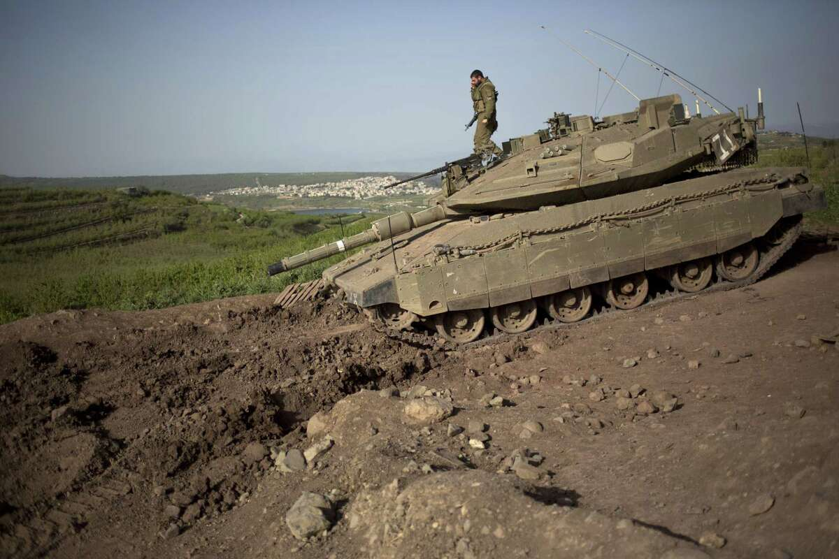 An Israeli soldier takes position near the border with Syria in the Israeli controlled Golan Heights on Monday. Israel's military said Sunday it launched an airstrike on its border with Syria after spotting militants carrying a bomb in the Israeli-held Golan Heights.