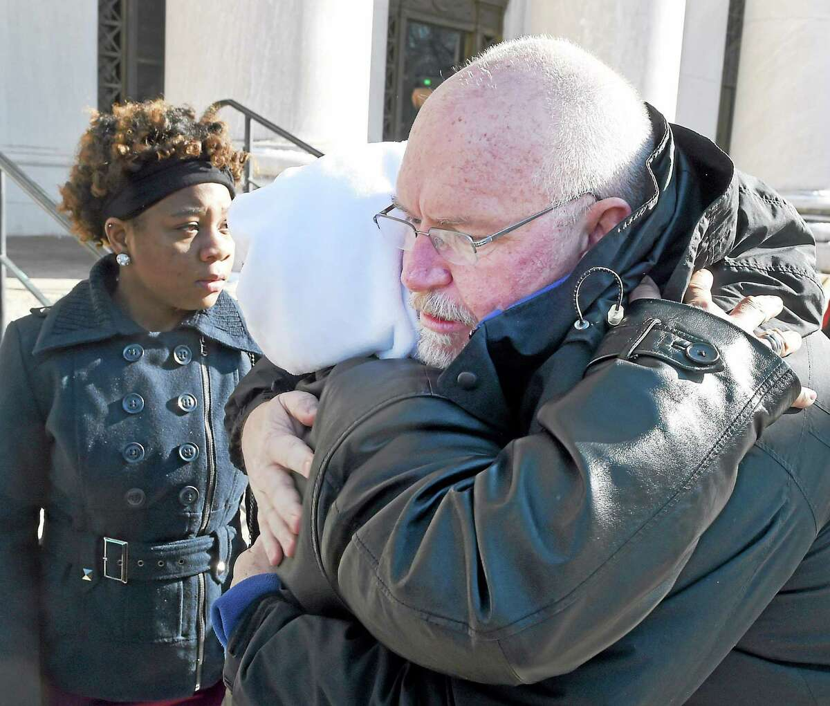 Lynn Roberson of New Haven and FBI Agent James Lawton hug outside the Federal Courthouse in New Haven after Hector Natal of New Haven gets life imprisonment sentence Wednesday, February 25, 2015 for the 2011 triple fatal arson fire at a New Haven apartment building. Roberson's sister Wanda was killed in the fire.