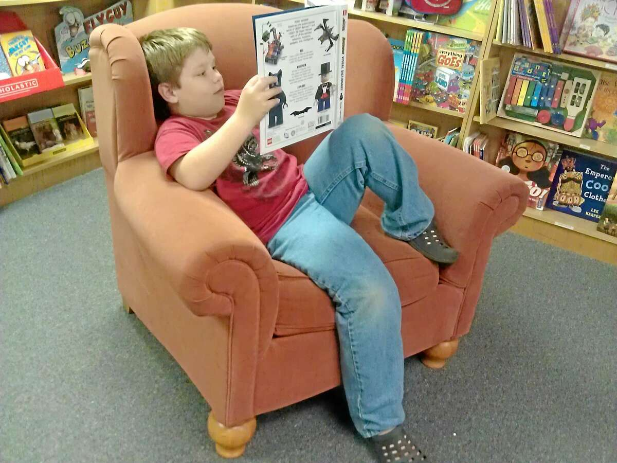 A boy reads at a tween reading event.
