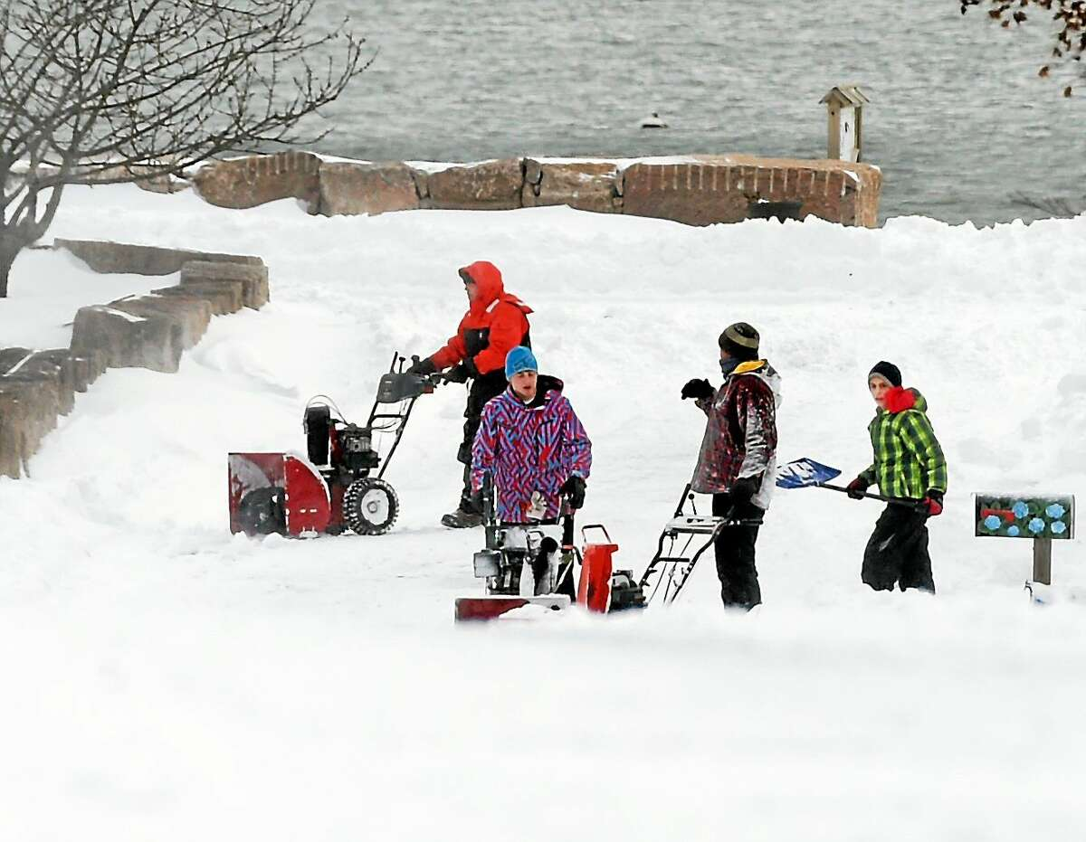 (Peter Hvizdak - New Haven Register) Men work on clearing snow on Fourth Ave. in the Hotchkiss Grove section of Branford in the aftermath of the blizzard Tuesday, January 27, 2015.