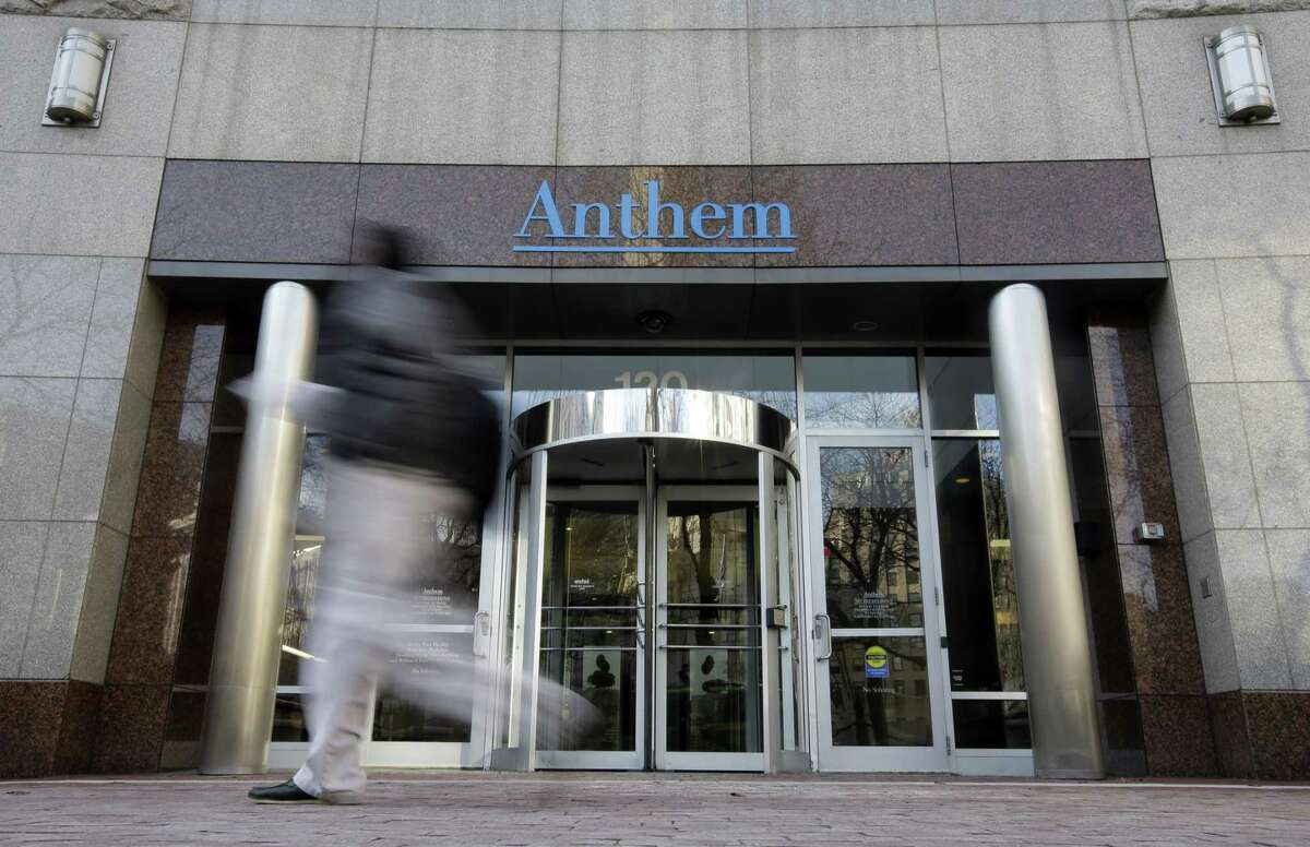 AP Photo/Darron Cummings, File In this Dec. 3, 2014 photo, a pedestrian walks past the corporate headquarters of health insurer Anthem, in Indianapolis.