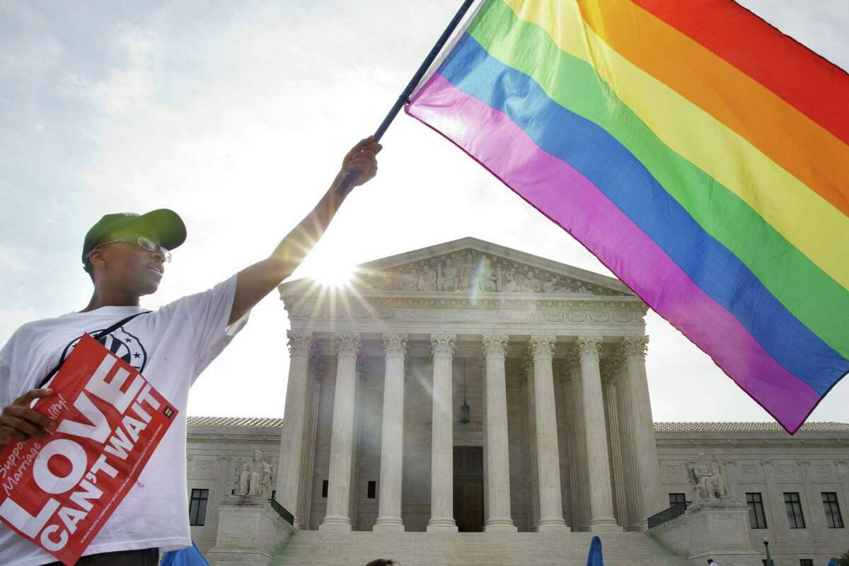 Associated Press Carlos McKnight of Washington, waves a flag Friday in support of gay marriage outside of the Supreme Court in Washington.