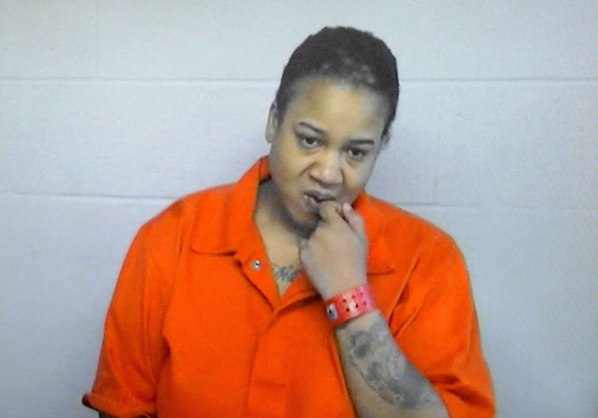 Mitchelle Blair stands during her video arraignment at the 36th District Court, Thursday, March 26, 2015, in Detroit. The Detroit woman charged with child abuse after the bodies of two of her children were found in her home freezer has been ordered to stay in jail Thursday unless she can post a $1 million bond.
