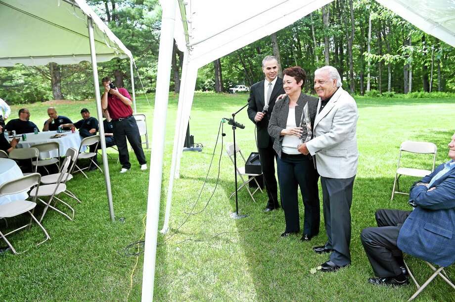 Left to right, Rogerio Branco, Senior Vice President of Supply Chain Management for the Eaton Corporation and Abby Lilly, Vice President of Supply Chain Management for the Eaton Corporation, award Jack Hillman, Sr., CEO of Precision Aerospace, the Supplier of the Year Award at a luncheon on the grounds of Precision Aerospace in Seymour  on 6/26/2015. Photo: (Arnold Gold-New Haven Register)