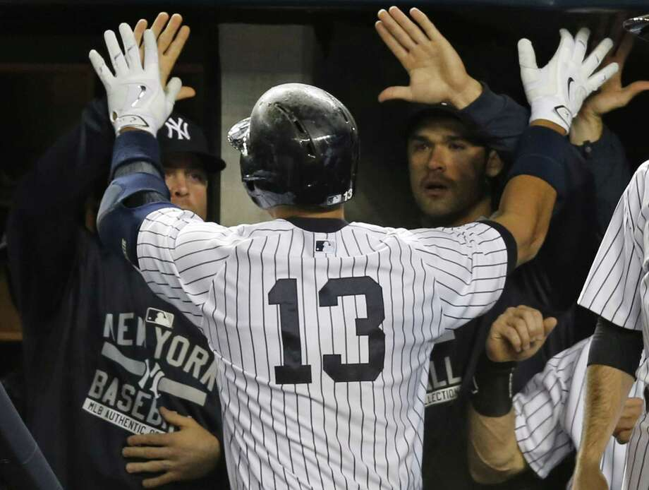 Yankees designated hitter Alex Rodriguez is greeted by teammates and coaches after hitting a first-inning solo home run on Sunday night. Photo: Kathy Willens — The Associated Press   / AP