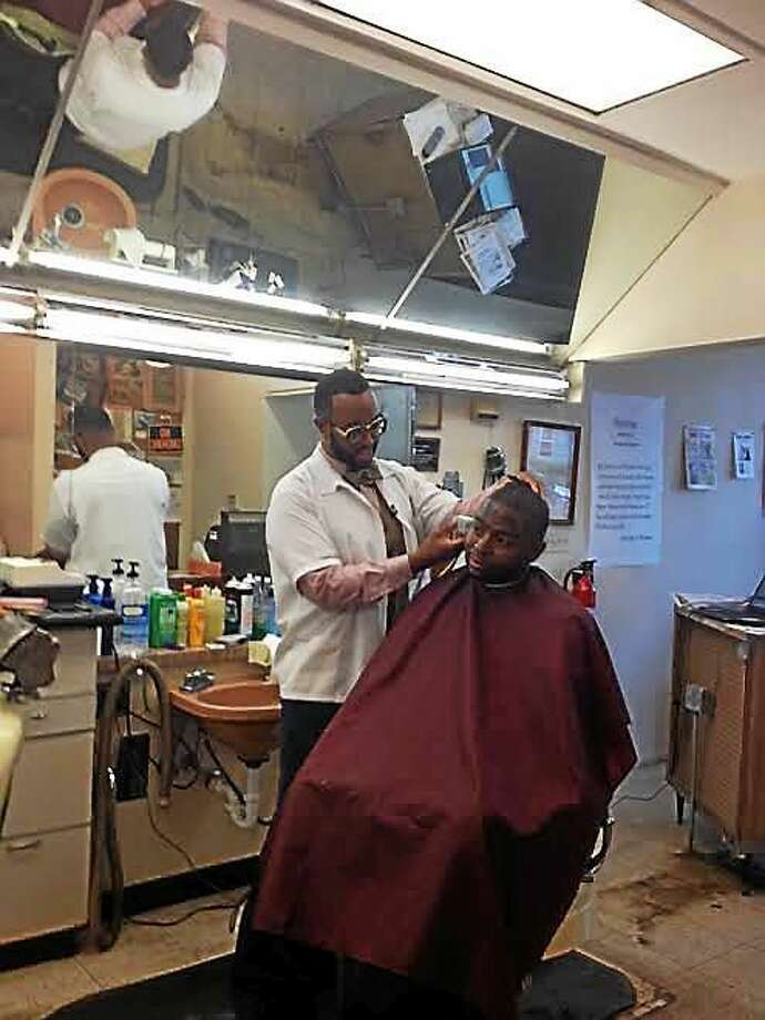 Clyde Thompson, 32, gives a new customer a hair cut at the former Reaves Barbershop Friday. Photo: (Mary O'Leary - New Haven Register)