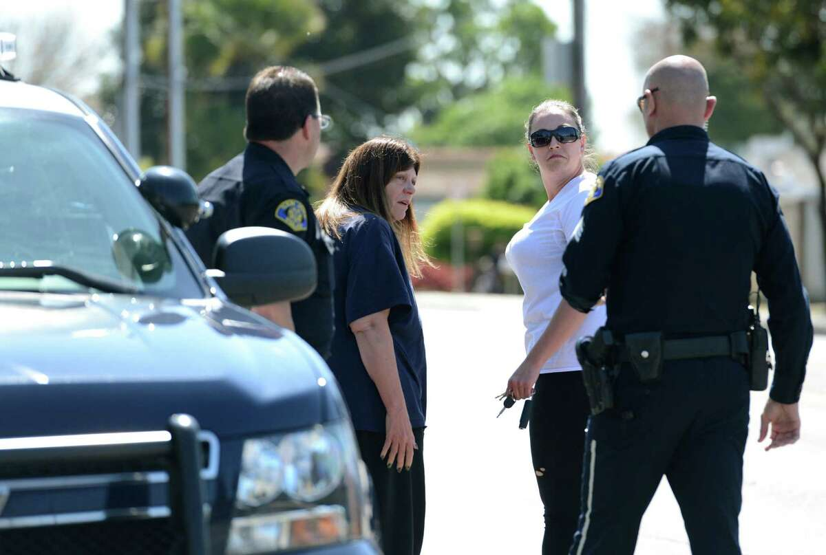 Two women talk with a San Jose police officers outside of the Senterville Terrace complex in San Jose, Calif., Wednesday, March 25, 2015. A man threatening to commit suicide unleashed a barrage of gunfire at the complex on Northern California officers called to check on him, killing officer Michael Johnson, a 14-year veteran of the San Jose Police Department on Tuesday. (AP Photo/San Jose Mercury News, Gary Reyes) MAGS OUT; NO SALES