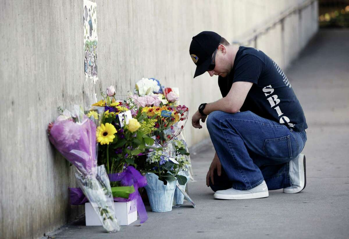 Officer Brandon Monlux, of the San Jose Police Department, pauses after dropping off flowers in front of a memorial for police officer, Michael Johnson, in front of the San Jose Police Department headquarters in San Jose, Calif., Wednesday, March 25, 2015. A man threatening to commit suicide unleashed a barrage of gunfire on Northern California officers called to check on him, killing Johnson, a 14-year veteran of the San Jose Police Department on Tuesday. (AP Photo/San Jose Mercury News, Gary Reyes) MAGS OUT; NO SALES