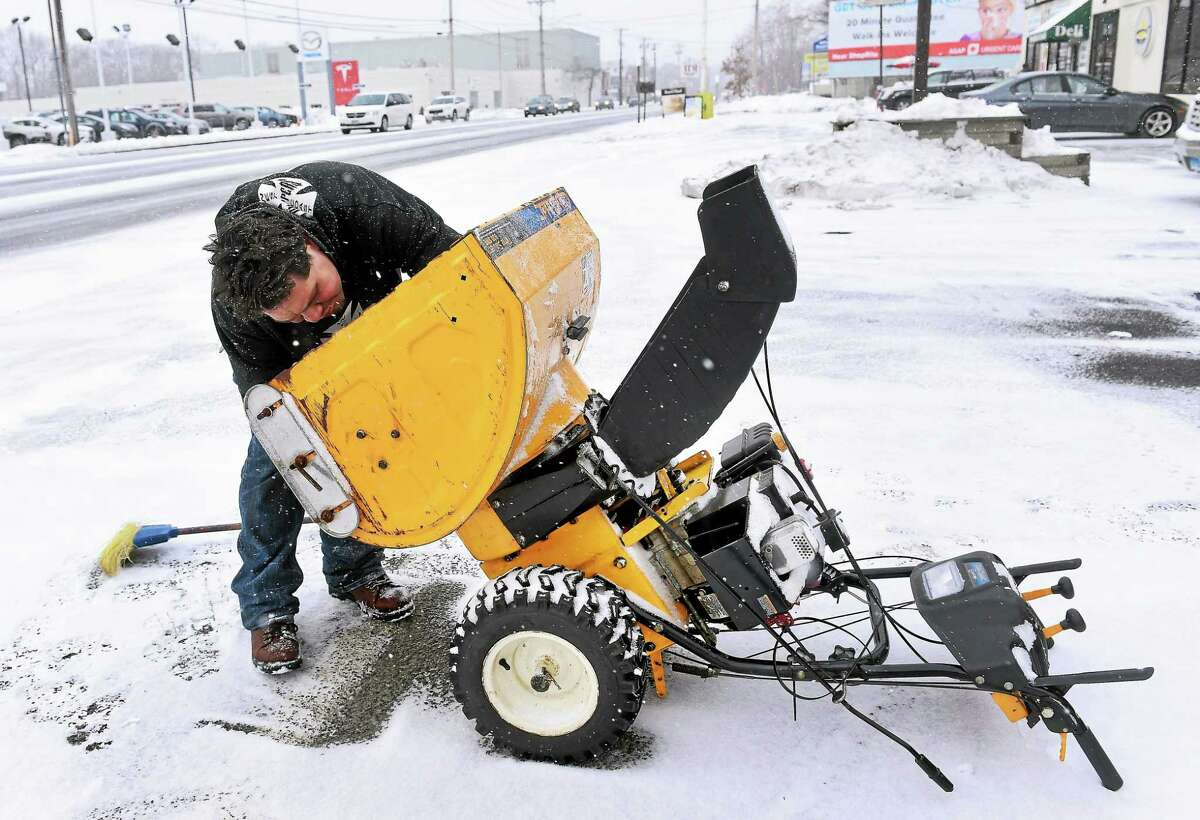 Joe Delgado replaces a part on a snow thrower in front of Milford Pawn in Milford on 1/26/2015.