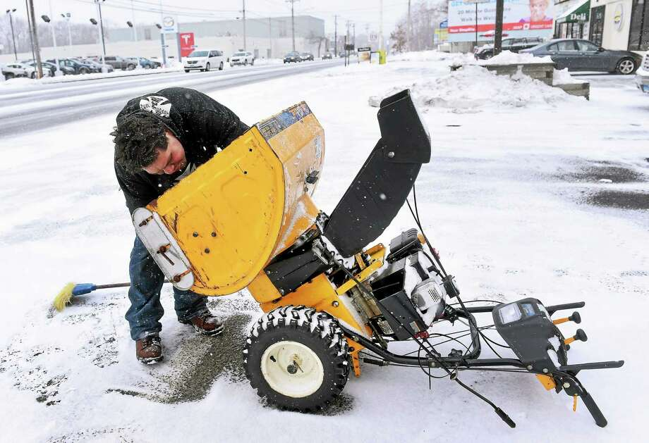 Joe Delgado replaces a part on a snow thrower in front of Milford Pawn in Milford on 1/26/2015. Photo: (Arnold Gold-New Haven Register)