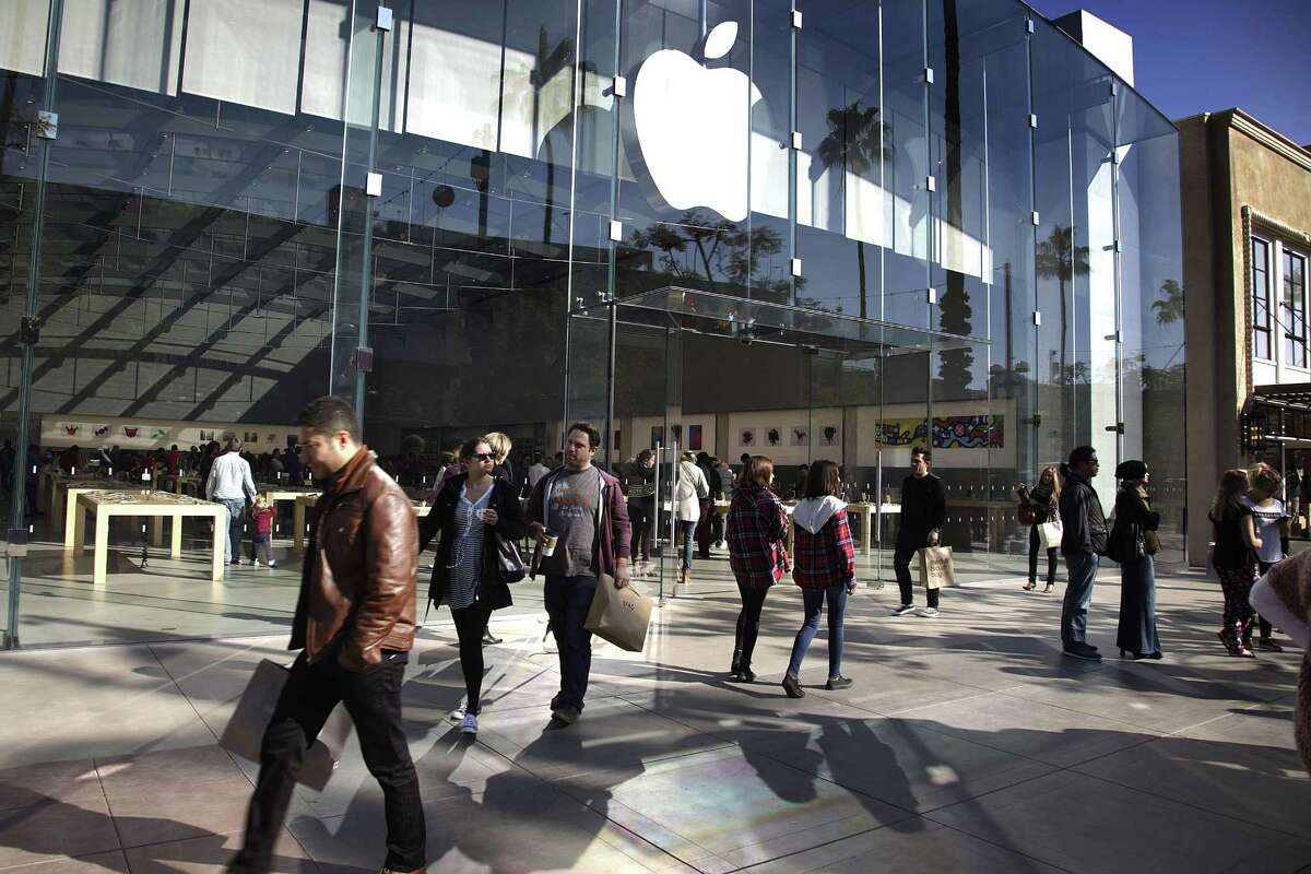 In this Jan. 3 photo, shoppers walk by the Apple Store along the the Third Street Promenade in Santa Monica, Calif.
