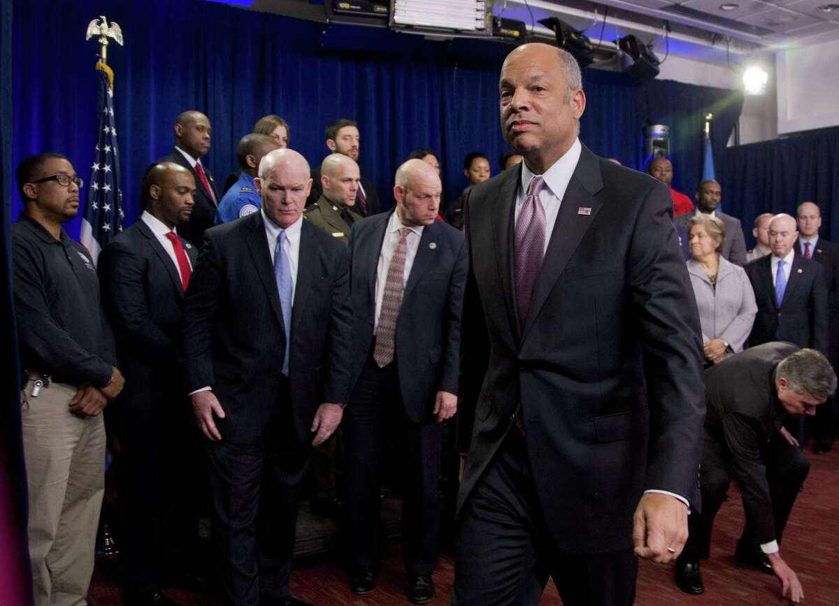 Homeland Security Secretary Jeh Johnson, front center, joined by the department employees, leaves a news conference in Washington Monday.