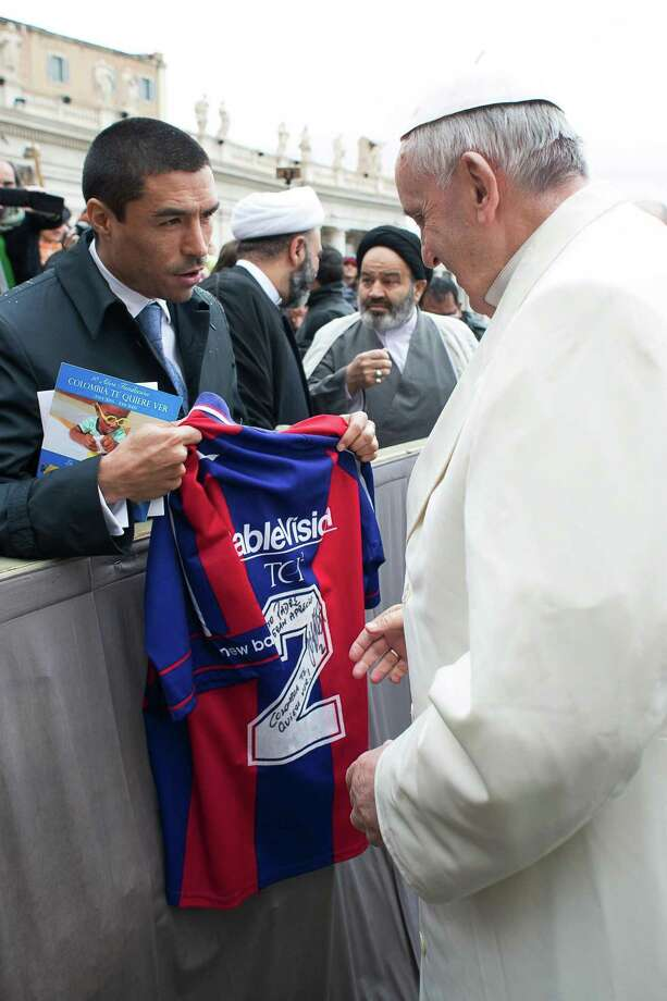 In this picture taken Wednesday, March 25, 2015 Pope Francis is presented with a San Lorenzo soccer team jersey by former Colombian player Ivan Ramiro Cordoba during the pontiff's weekly general audience in St. Peter's square at the Vatican. (AP Photo/L'Osservatore Romano, Pool) / L'Osservatore Romano Pool