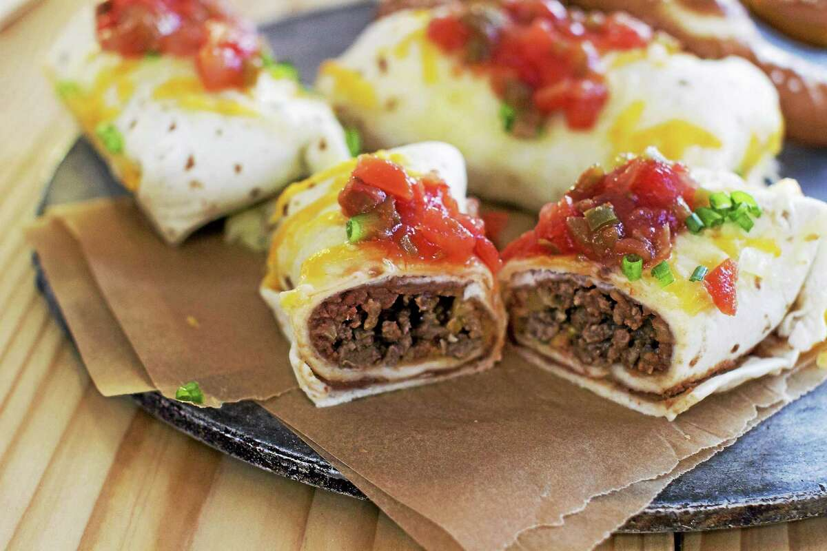 This Dec. 15, 2014 photo shows mini bean and beef burritos in Concord, N.H. To make burritos into a finger food, use small flour tortillas. (AP Photo/Matthew Mead)