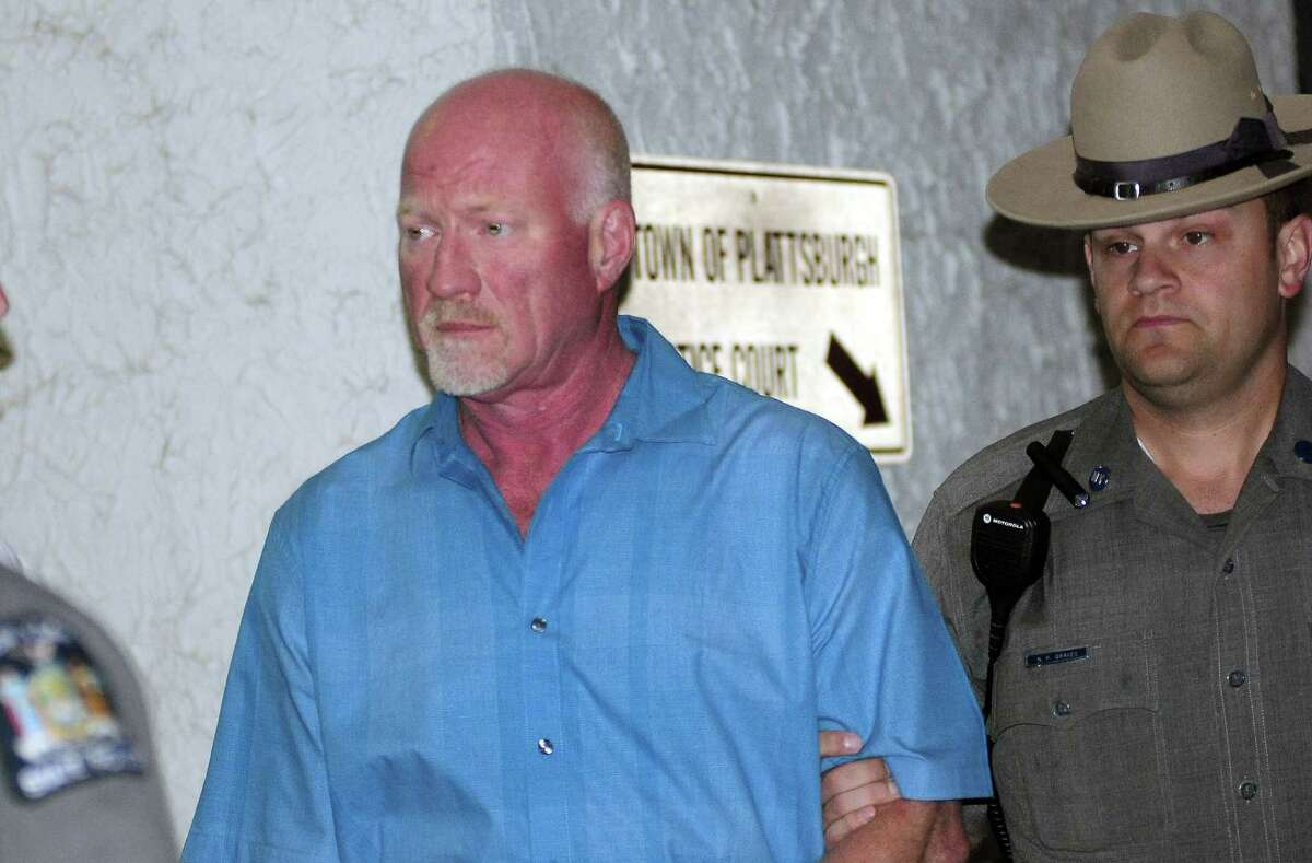 A New York State Police officer escorts suspended Clinton Correctional Facility guard Gene Palmer, left, from Plattsburgh Town Court in Plattsburgh, N.Y., Wednesday, June 24, 2015. Palmer is believed to have delivered tools inside frozen meat to two Clinton Correctional Facility inmates before they escaped on June 6.