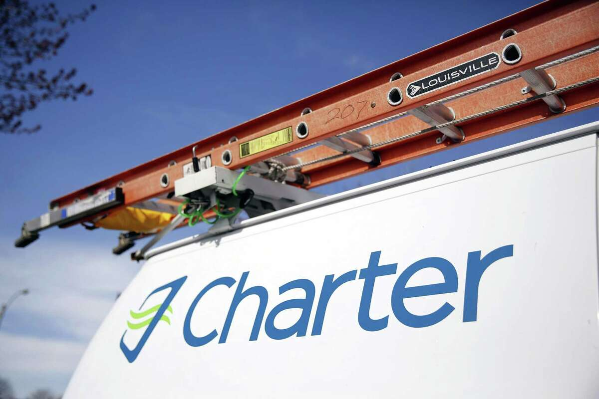 This April 1, 2015 photo shows a Charter Communications van in St. Louis. Charter Communications is close to buying Time Warner Cable for about $55 billion, two people familiar with the negotiations said Monday, May 25, 2015.