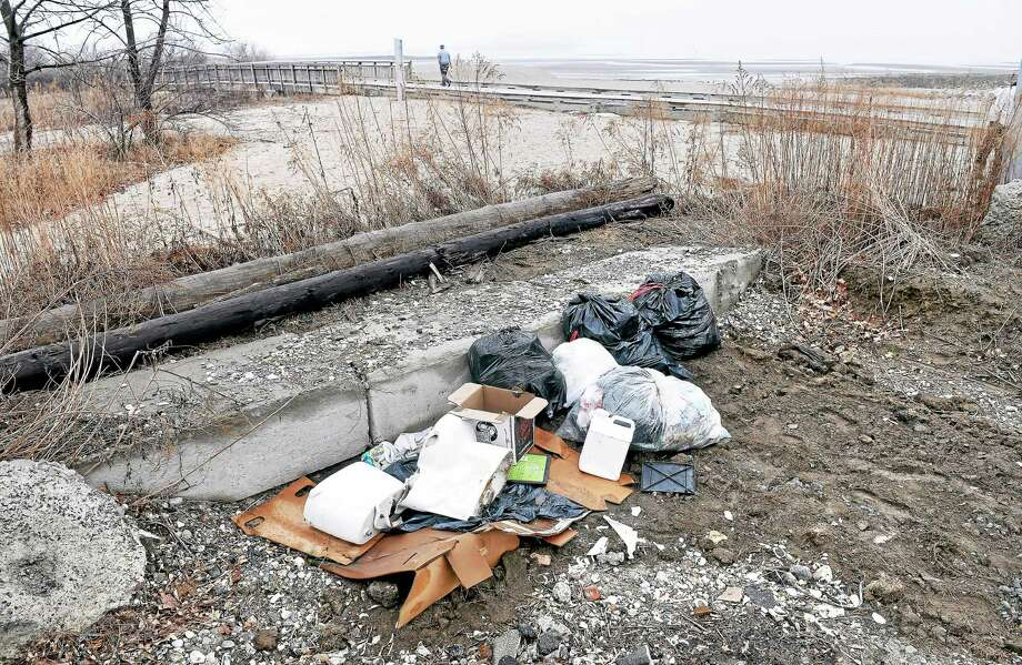 Trash collected from the western side of Silver Sands State Park waits to be collected at the edge of Walnut Beach Park in Milford Friday. The boardwalk connecting the two parks is in the background. Photo: Arnold Gold — New Haven Register