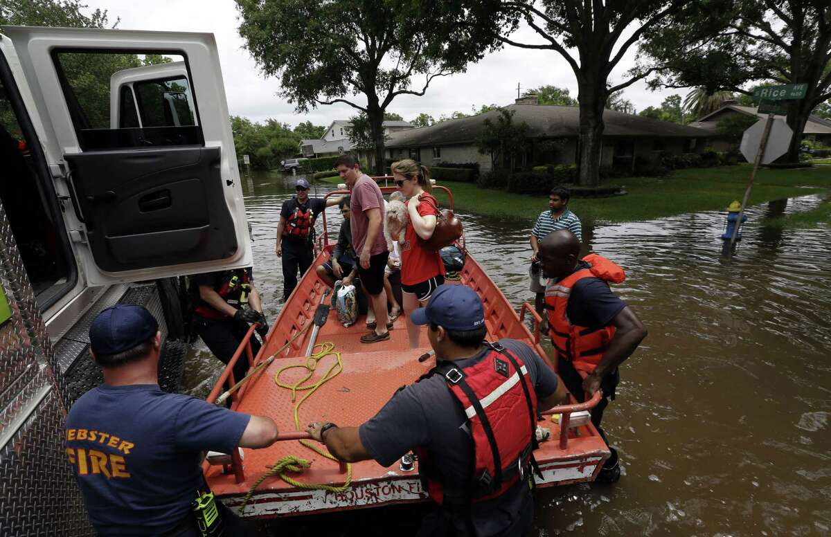 Members of the Houston and Webster Fire departments help residents evacuate through the floodwaters surrounding their homes in Houston Tuesday. Heavy rain overnight caused flooding and closure of sections of highways in the Houston area.