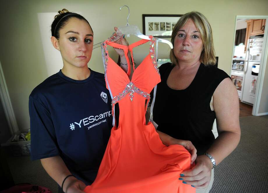 In this photo taken May 11, Shelton High School sophomore Kylee Opper, 15, left, and her mom Tricia Marini, hold one of two prom dresses that they purchased which have been deemed inappropriate at the school in Shelton. Photo: The Connecticut Post Via AP   / The Connecticut Post