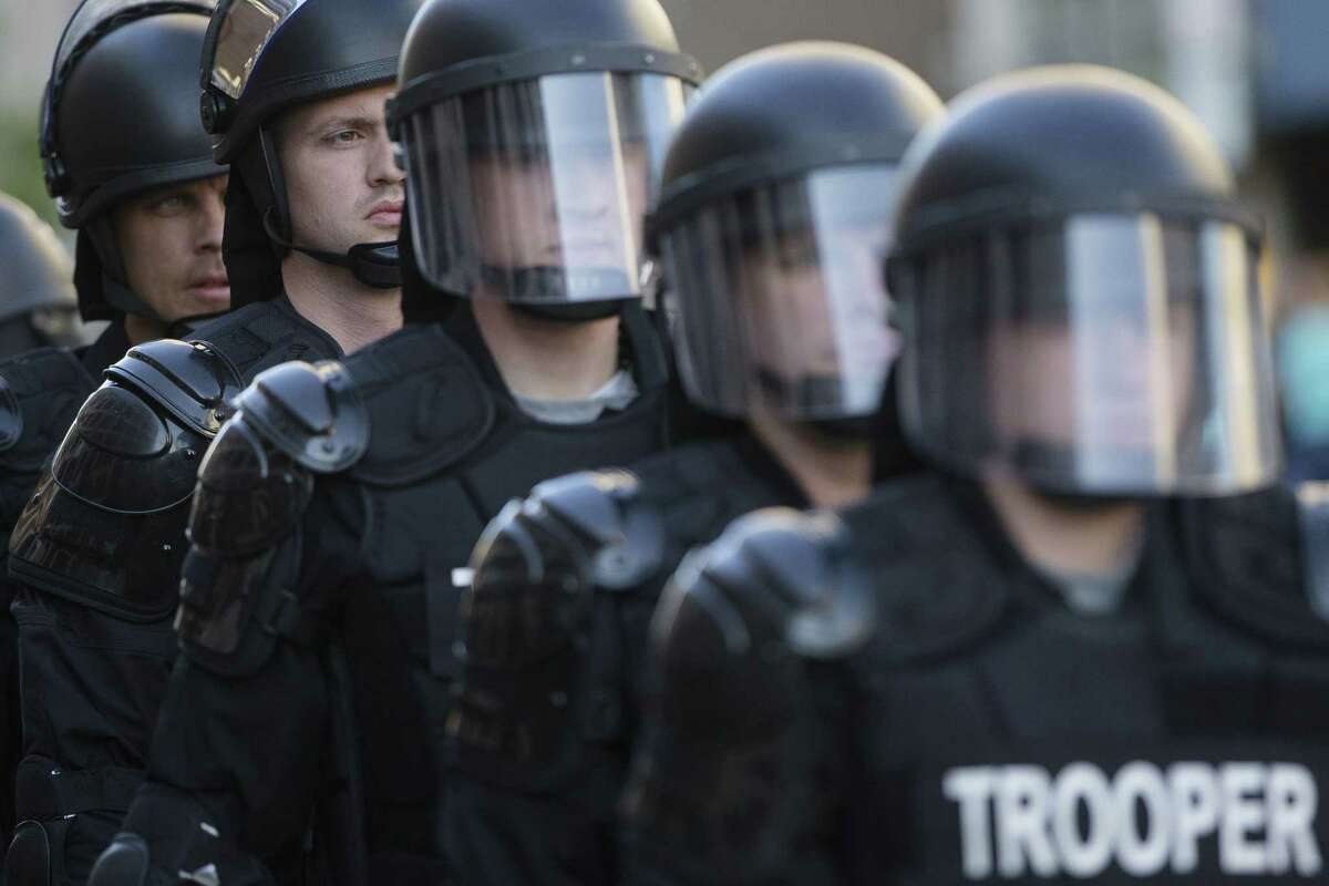 In this May 23, 2015 photo, riot police stand in formation as a protest forms against the acquittal of Michael Brelo, a patrolman charged in the shooting deaths of two unarmed suspects in Cleveland.