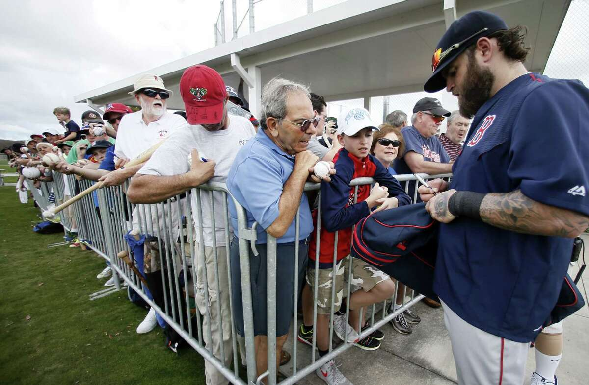 Boston Red Sox's Mike Napoli signs autographs after a workout at baseball spring training in Fort Myers Fla., Monday Feb. 23, 2015. (AP Photo/Tony Gutierrez)